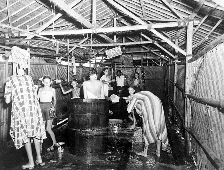 Vrouwen en kinderen wassen zich in het vrouwen-kamp Kampong Makassar in Meester Cornelis (Batavia), na de capitulatie van Japan in 1945. Beeld Tropenmuseum, part of the National Museum of World Cultures