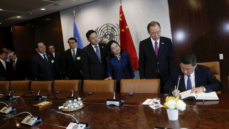 De Chinese president Xi Jinping tekent het gastenboek voordat hij secretaris-generaal Ban Ki-moon ontmoet in het VN-hoofdkwartier in Manhattan. Beeld REUTERS