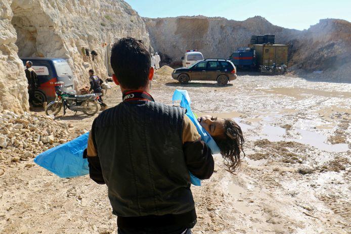 Een man draagt het dode lichaampje van een kind na de gifgasaanval in de Syrische stad Khan Sheikhoun in april.