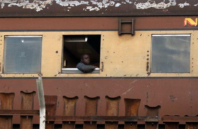 Een Zimbabwaan in juni van dit jaar in Harare aan boord van een vervallen trein. Beeld REUTERS