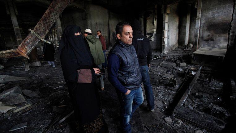 Libische strijders staan temidden van de puinhopen van wat eens het huis van Kaddafi was. Beeld AP