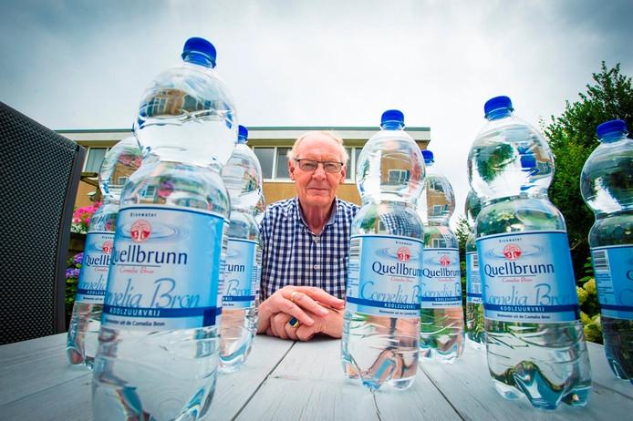 Nico Fortgens uit Zevenhuizen. met zijn ingekochte water. Hij drinkt liever geen leidingwater waar een poepbacterie in zit. Foto: Maarten Sprangh