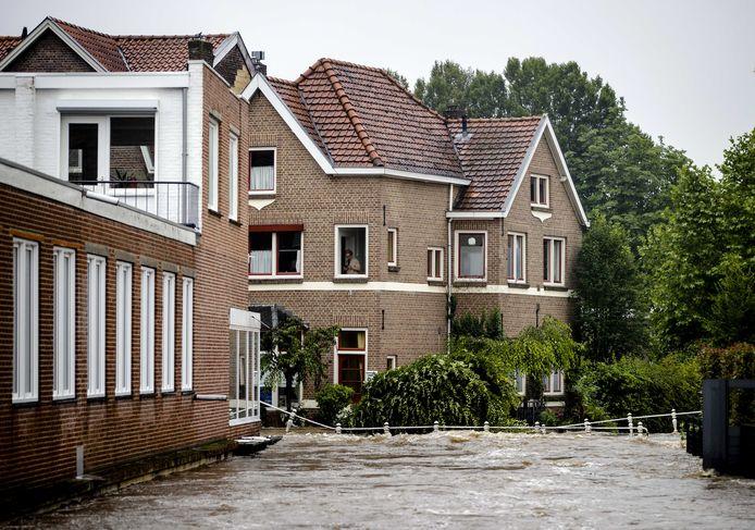 Een ingestorte brug in het centrum van Valkenburg. Door het almaar stijgende hoge water als gevolg van de de overstroming van de Geul zijn straten ondergelopen.