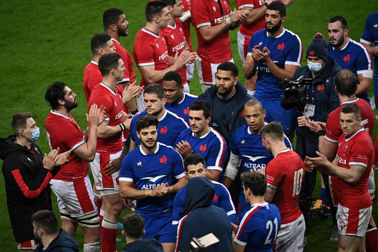 De Welshe spelers vormen een erehaag voor de Franse overwinnaars in het Prinsenpark. Beeld AFP