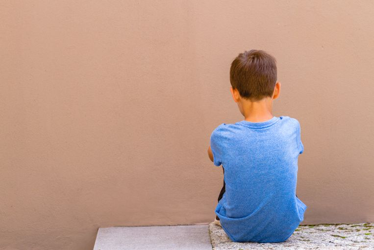 Sad alone boy sitting on the ground behind the wall outdoor.
