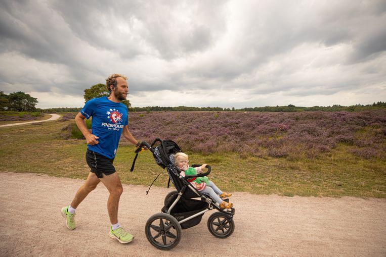 Een hardloper met zijn kind op de Zuiderheide nabij Hilversum. Beeld Hollandse Hoogte / Caspar Huurdeman Fotografie