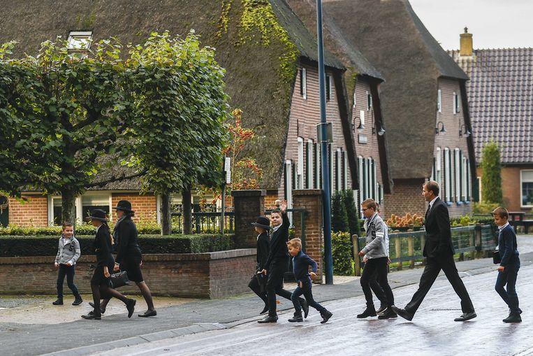 Kerkgangers komen aan bij de Hersteld Hervormde Kerk in het diepgelovige dorp Staphorst.  Beeld ANP