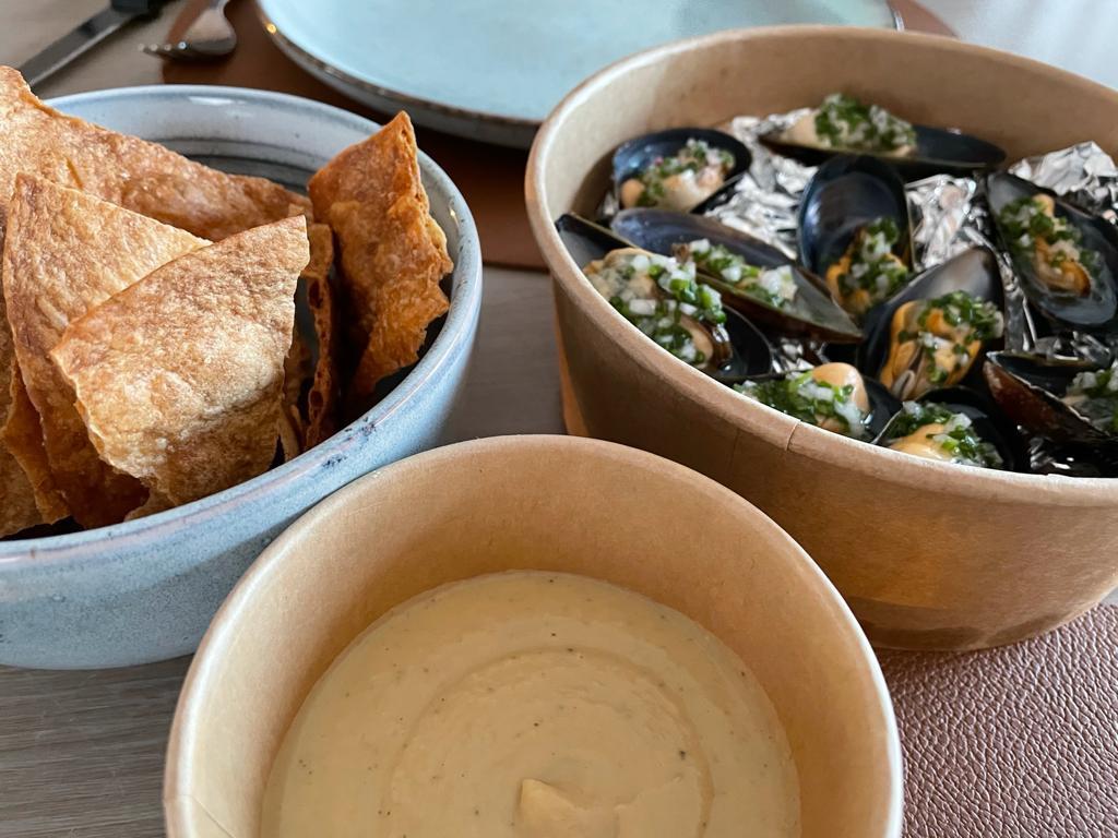 De crackers met hummus staan de hele tijd op tafel, ook bij de mosseltjes.
