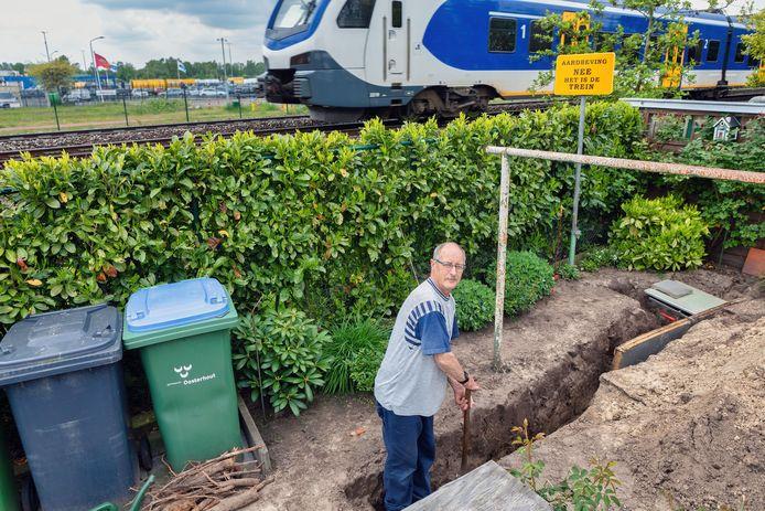 Jos Gommeren uit Dorst graaft een sleuf waar hij platen piepschuim in stopt om de trillingen van treinen bij zijn huis te verminderen.