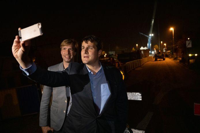 Schepenen Bert Wollants (N-VA) en Rik Verwaest (N-VA) nemen nog  snel even een selfie tijdens het plaatsen van het eerste brugdeel van de fietsbrug.