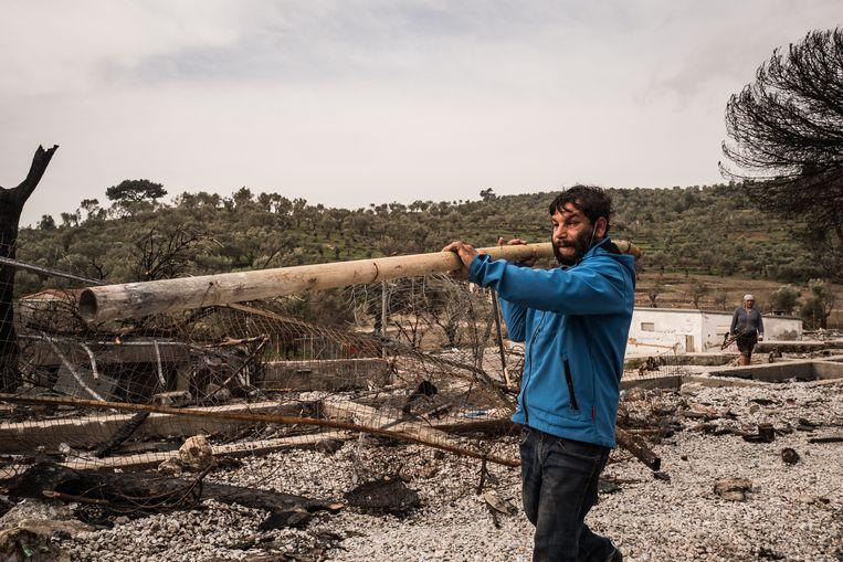 Een man neemt materiaal mee uit het verwoeste, oude kamp. Beeld Nicola Zolin