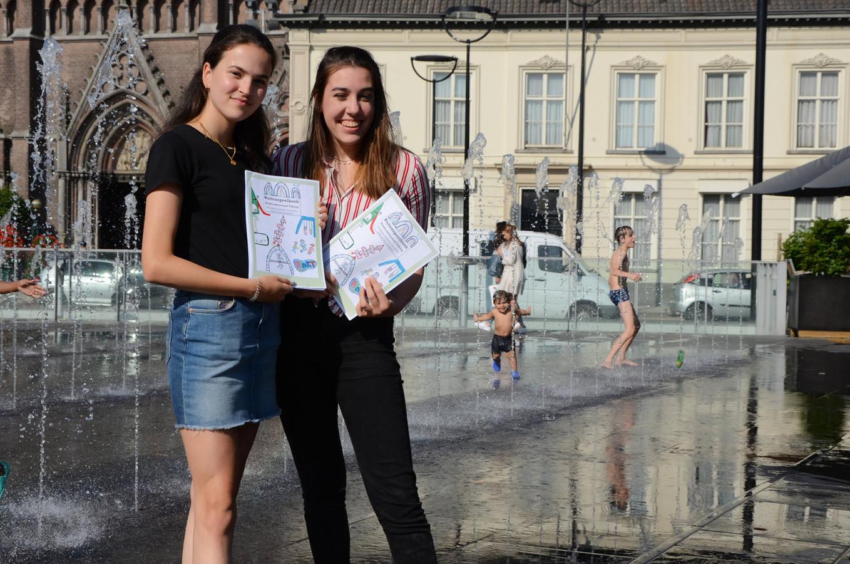 Fleur (rechts) en Aafje poseren met hun boek op de Heuvel in Tilburg: 'Voor spelen heb je niet veel nodig. Dat past bij KART. Ervoor zorgen dat alle kinderen mee kunnen doen.'