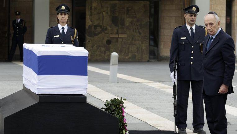 Zijn kist, gehuld in de wit-blauwe Israëlische vlag met davidster, is in de middag opgebaard op het plein van de Knesset, waar ook president Shimon Peres (R) een krans neerlegde Beeld reuters