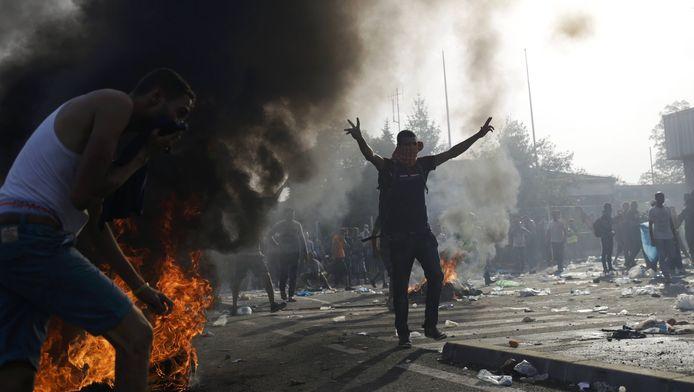 Migranten tarten de Hongaarse grenspolitie, terwijl ze worden bestookt met traangas en waterkanonnen.