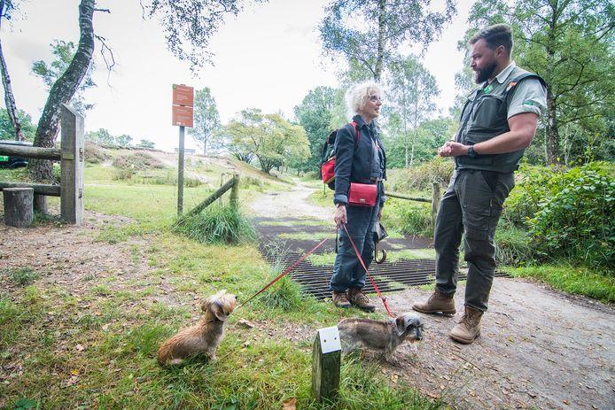 Een boswachter in gesprek met de eigenaresse van twee hondjes. (Archieffoto)