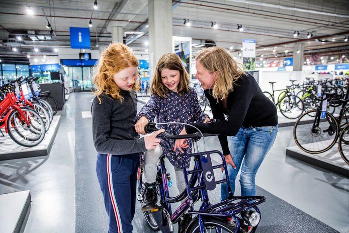 Isabel (8) probeert een fiets uit bij fietsenwinkel Mantel in Utrecht. Zus Annemijn en moeder Lottie helpen een handje.