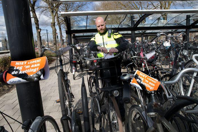 Agent Niels de Wilde hangt waarschuwingsbriefjes op aan de fietsen bij station Zevenaar.