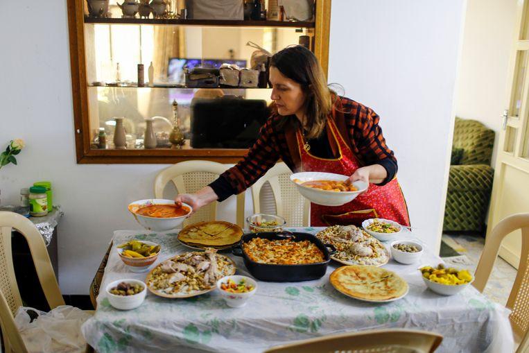 Een vrouw serveert eten in haar huis in Mosul (Irak) waar zij, haar man en twee zoons in 2014 uit werden verdreven door IS. De graffiti op de deur, 'Islamitische Staat blijft altijd bestaan', heeft het christelijke gezin laten staan als herinnering. Van de 50.000 christenen in Mosul zijn slechts tientallen teruggekeerd sinds IS er drie jaar geleden werd verslagen.  Beeld REUTERS