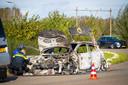 Politiemensen onderzoeken de uitgebrande auto aan de IJsselcentraleweg.
