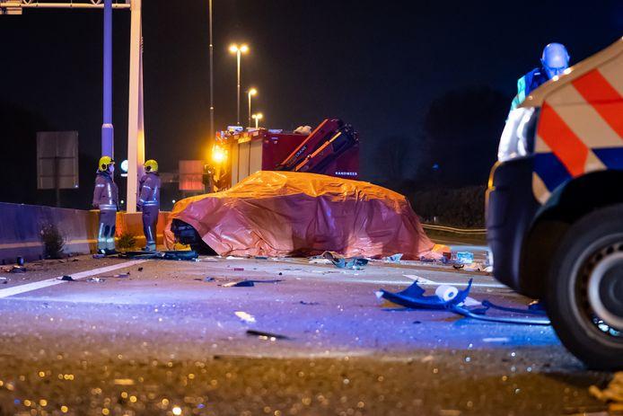 De politie legde een zeil over de auto die over de kop sloeg en waarin een overleden persoon zat.