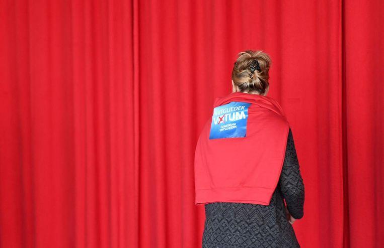 Een SPD-lid heeft een sticker op haar trui geplakt, waarin zij haar partijleden op het partijcongres vorig weekend oproept om te stemmen voor de GroKo. Beeld afp