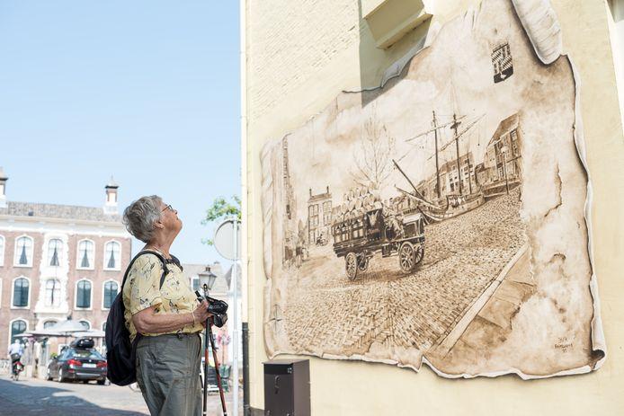 Een voorbijganger bewondert de muurschildering.