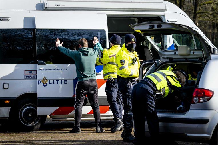 Een politieagent fouilleert een man. Beeld ANP