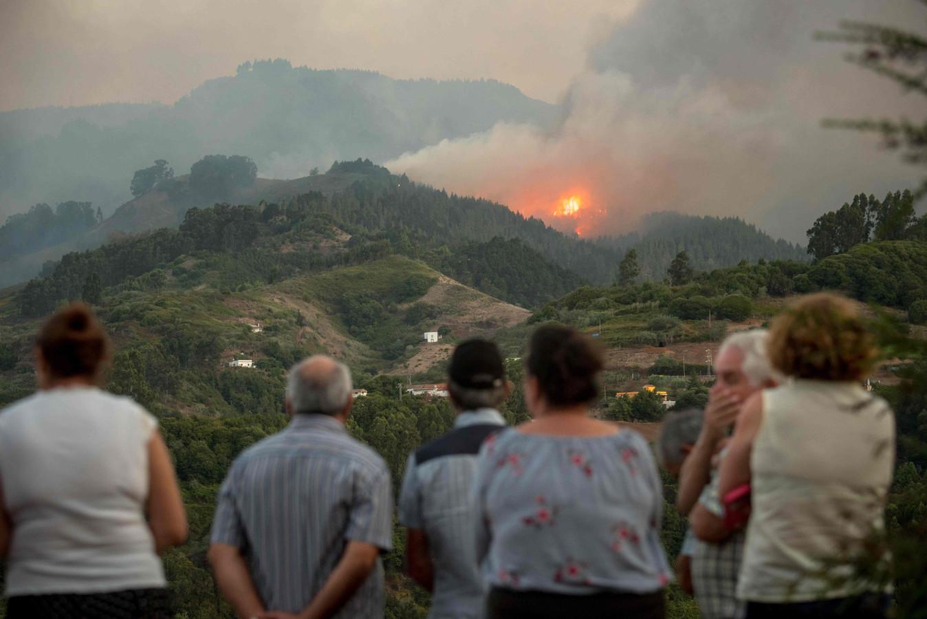 Inwoners van Montana Alta kijken geschrokken toe hoe het vuur zich verspreidt.