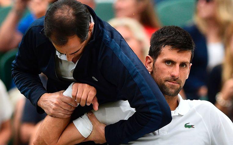 Novak Djokovic wordt behandeld op Wimbledon. Beeld afp