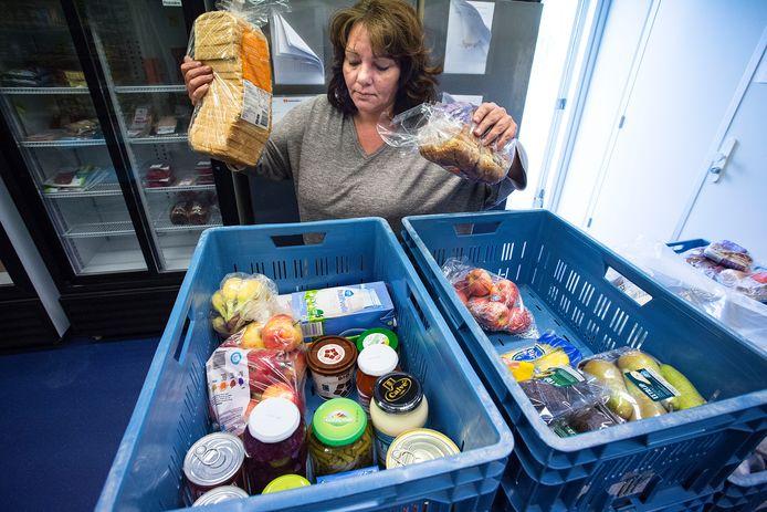 Carine Cassauwers laat zien hoe een voedselpakket voor een gezin met twee kinderen er gemiddeld uitziet