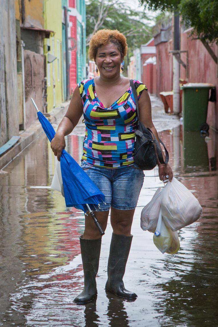 Een vrouw in de natgeregende straten van Willemstad. Beeld Cigdem Yuksel