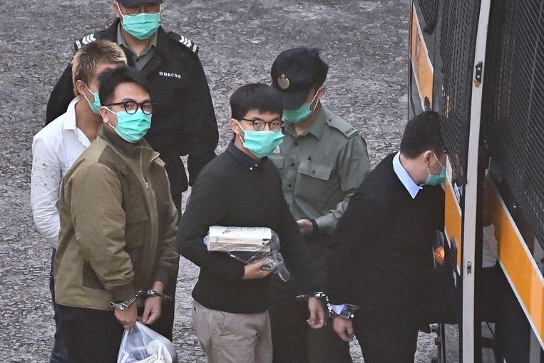 Activisten Ivan Lam (links) en Joshua Wong (midden) worden een politiebusje in geleid.  Beeld AFP
