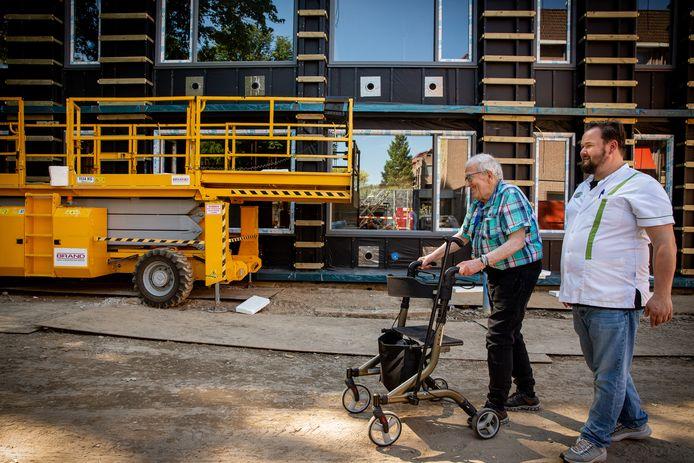 Meneer Leenders van 77 krijgt een rondleiding over het terrein. In de achtergrond de nieuwbouw. Hij woont zelfs sinds 9 april in La Verna en gaat binnenkort over naar de nieuwbouw.