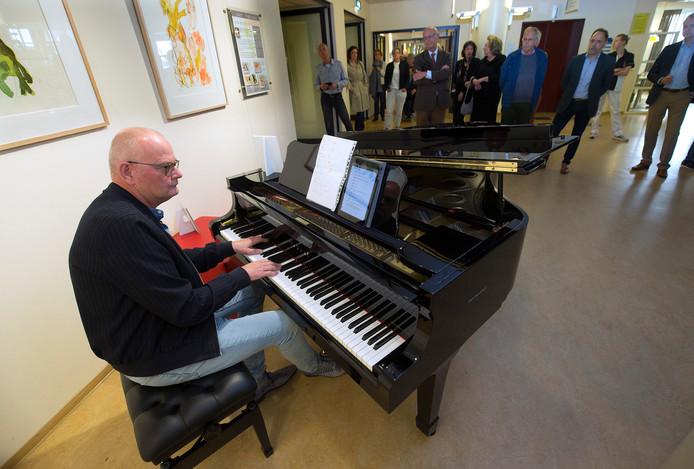 Pianist Maarten Knikkink, in het dagelijks leven gipsmeester in het Slingeland Ziekenhuis, achter de vleugel bij de bezoekersruimte.
