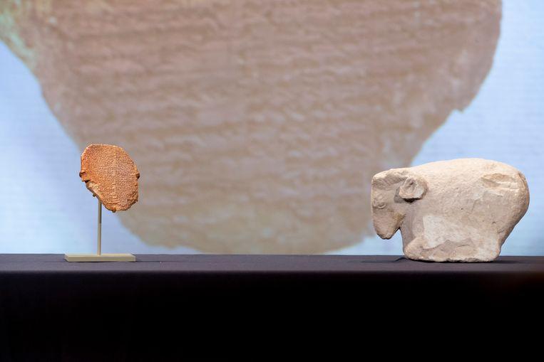 Het kleitablet waarop een deel van het Gilgamesj-epos beschreven staat, naast een beeldje van een ram. Beeld EPA