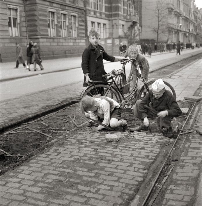 Inwoners verzamelen in de Hongerwinter tramspoorbielzen nabij het Barlaeus Gymnasium om als brandhout te gebruiken, Amsterdam (1944-45)