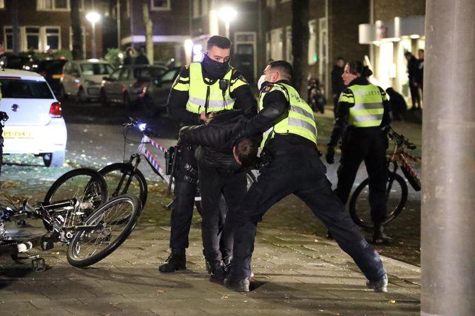 Politie-agenten houden een jonge man in bedwang in de Geitenkamp in Arnhem.