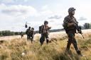 Gewapende militairen stellen de omgeving veilig en begeleiden artsen en verpleegkundigen.