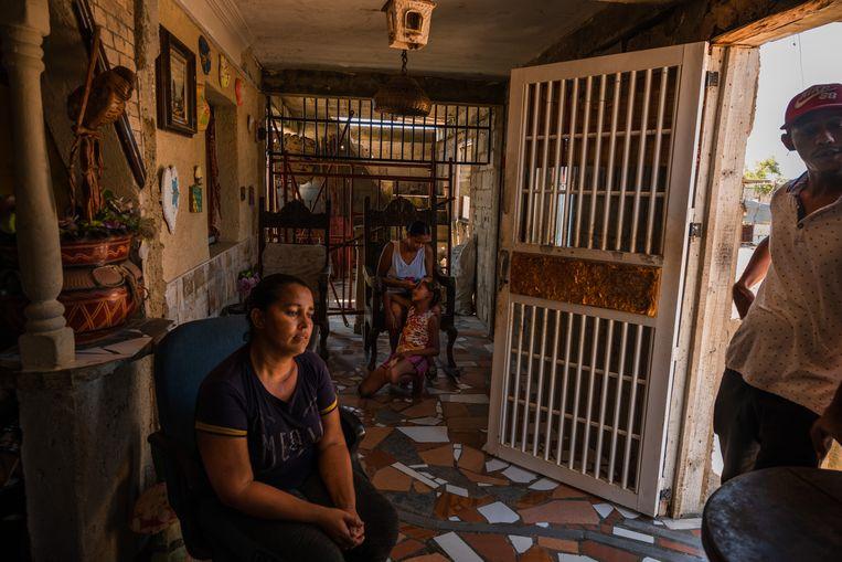 Een gezin in Tucacas, vlak bij de grootste raffinaderijen. Bewoners verwarmen hun huizen met her en der gesprokkeld brandhout. Beeld NYT