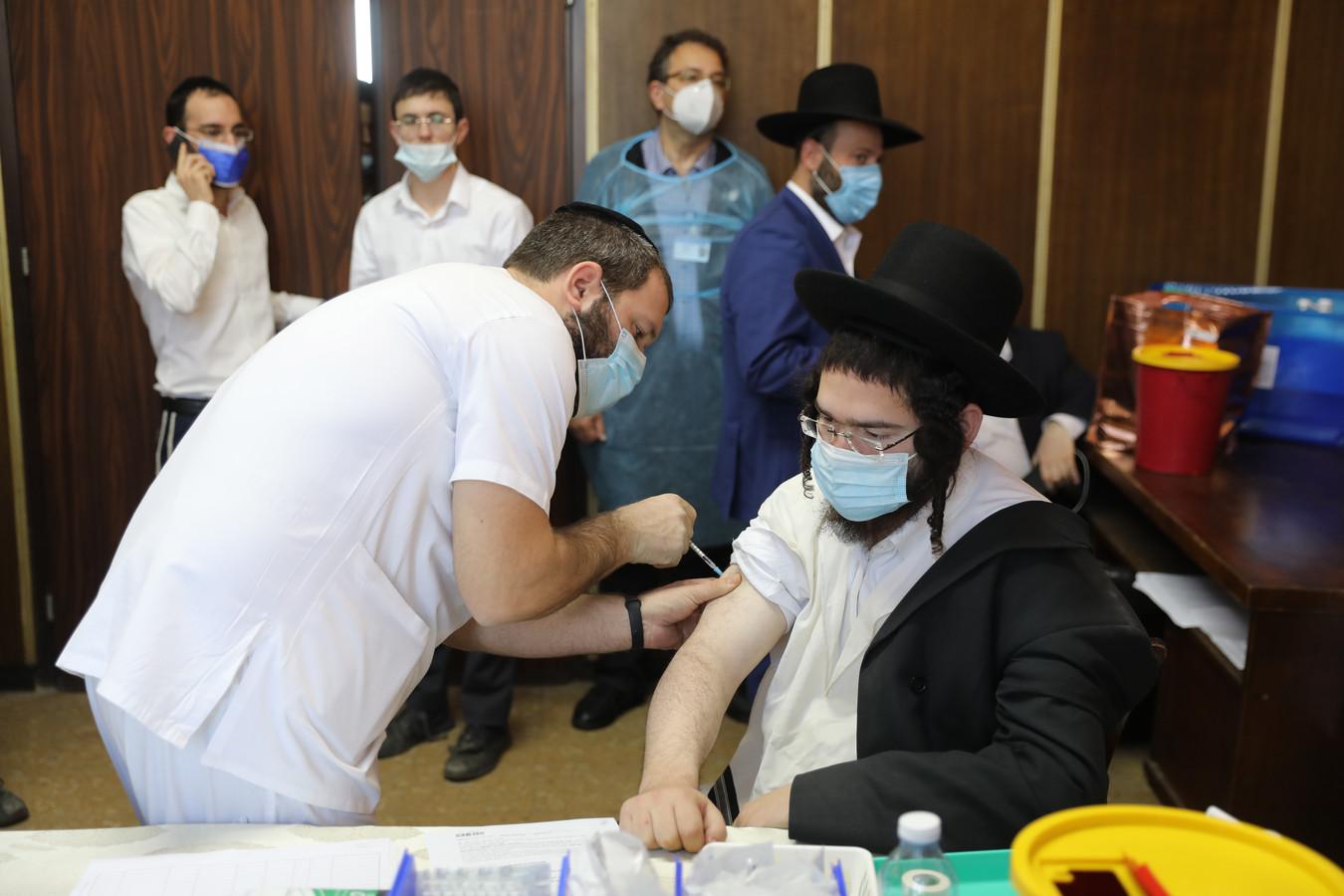 Een man laat zich vaccineren in het Ichilov Medical Center in de orthodox-joodse stad Bnei Brak.