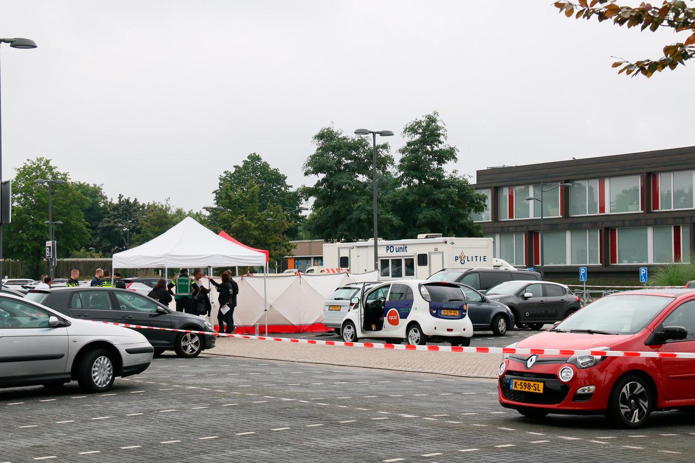 Rood-witte linten, witte schermen en veel politiemensen op de parkeerplaats van het Almelose ziekenhuis.