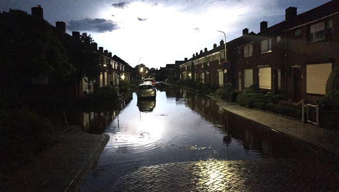Wateroverlast in een straat in Sint Philipsland. Delen van Nederland zijn in de geteisterd door noodweer. Door de regenval liepen lokaal straten onder water