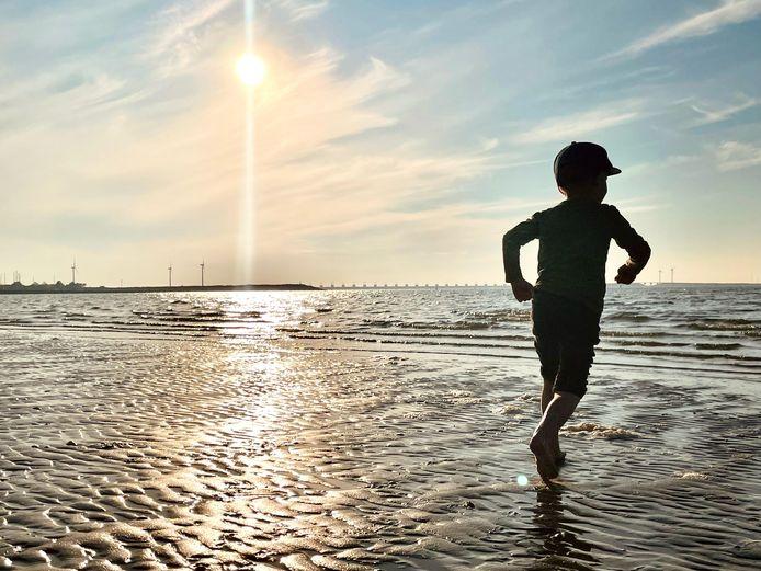 BROEKJE IN DE BRANDING De vierjarige Jesse van den Broek rent uitgelaten over het strand bij het Zeeuwse Kamperland. De laatste zonnestralen van de dag vergezellen hem. Het begin van een weekend vol familieplezier.