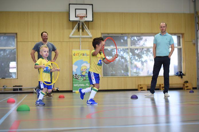 Hardlopen zonder bal waarbij de hoepel als stuur fungeert. Vaders kijken geamuseerd toe.