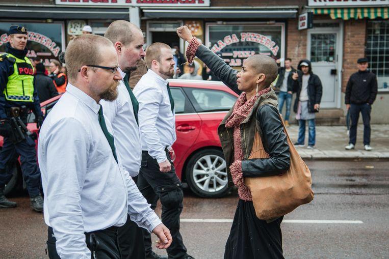 Een vrouw, met opgeheven vuist, keert zich tegen een demonstratie van de Nordiska Motståndsrörelsen (NMR) in Borlänge in 2015. Beeld BELGAIMAGE