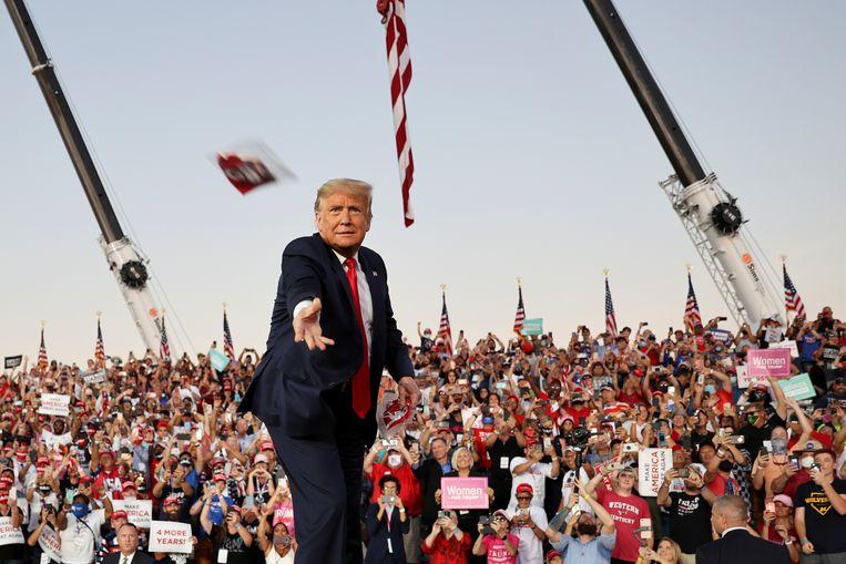 Trump gooit een mondkapje van het podium tijdens een rally in Orlando, oktober 2020.  Beeld Reuters