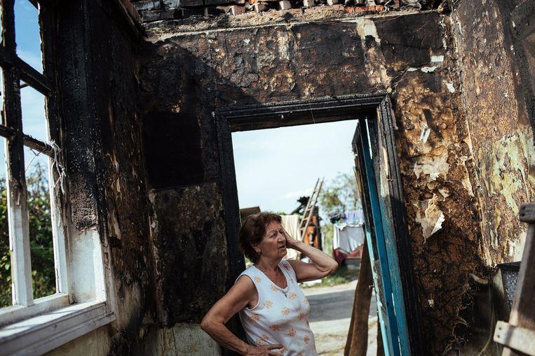 Een vrouw in Slavjansk bekijkt de schade aan haar huis nadat het werd getroffen in het spervuur tussen Oekraïense soldaten en Russische seperatisten. Beeld EPA