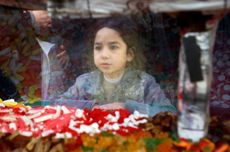 Een meisje kijkt door een etalageraam naar uitgestalde snoepwaren. Beeld Reuters
