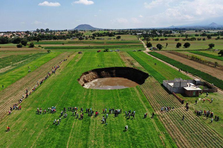 Het lijkt een Ufo-landingsplaats waar het dorp voor uitgelopen is, of een krater geslagen door een meteoriet. Wat Mexicaanse boeren aantroffen op een akker bij het dorp Santa Maria Zacatepec is evenwel een plotseling ontstaan sinkhole, oftewel een zinkgat.  Beeld AFP