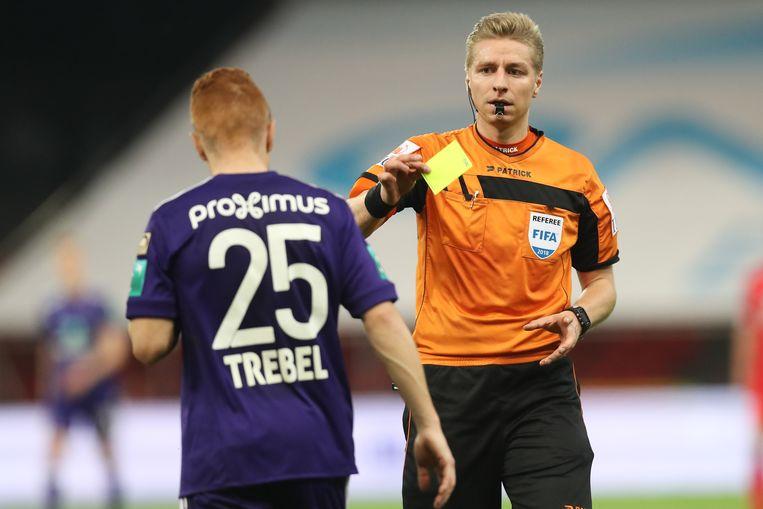 Lawrence Visser geeft Anderlecht-speler Adrien Trebel een gele kaart tijdens Standard-Anderlecht.